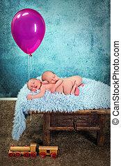 Newborn baby twins with balloon