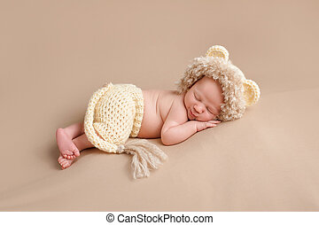 A smiling three week old newborn baby boy wearing a crocheted lion costume. Shot in the studio on a khaki colored background.