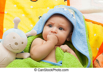 Newborn baby with the hand in his mouth.