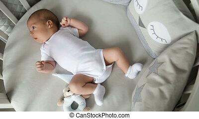 Newborn boy lies in a round bed