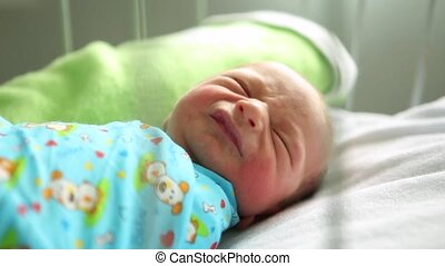 Newborn boy sleeping in her bed in the maternity hospital. cry