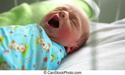 Newborn boy sleeping in her bed in the maternity hospital. yawns