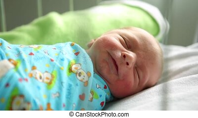 Newborn boy sleeping in her bed in the maternity hospital. He wants to eat