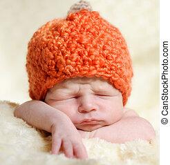 newborn boy wearing pumpkin hat