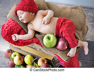 Newborn child sleeping on the box of apples