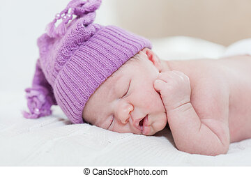 newborn child with a ridiculous violet hat sleeps, lying on a stomach