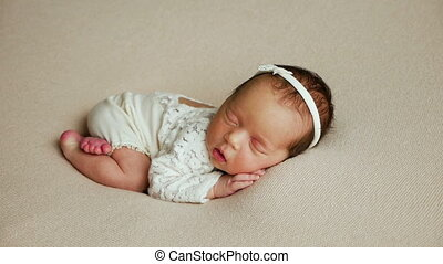newborn girl in a dress lies in bed