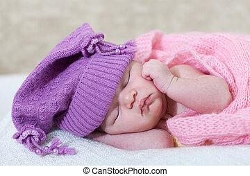 newborn girl in a violet hat sleeps under a pink cape