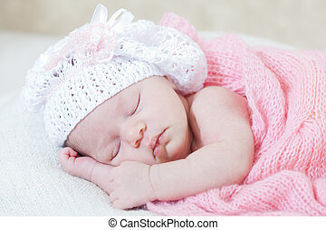 newborn girl sleeps under a knitted pink cape