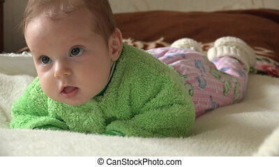 Newborn Girl Watching TV on the Bed