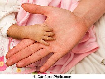 Newborn hand - Tiny newborn baby hand against and adult...