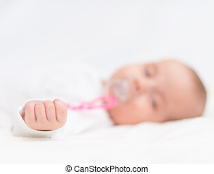 Newborn little baby with dummy sleeping on the bed.