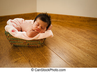 Newborn naked sleeping on a basket