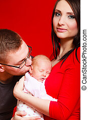 Newborn on mother chest father kissing baby