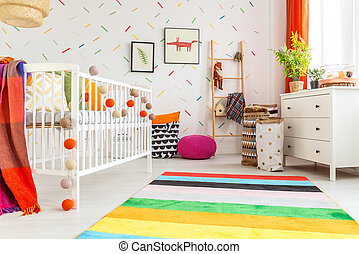 Newborn room in scandi style with white wall and rug