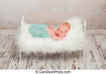 newborn sleeping on cot with white soft blanket
