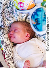 Newborn baby girl sleeping in the cradle swing.