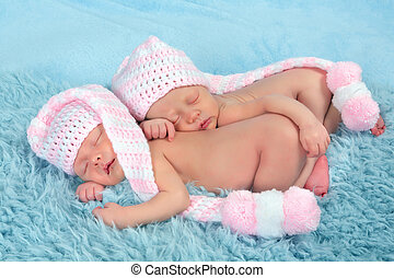 Newborn twins with pink hats