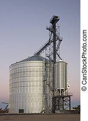 newly constructed metal grain silo and elevator against clear sky