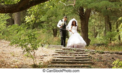 Newly-married couple go down on an old stair