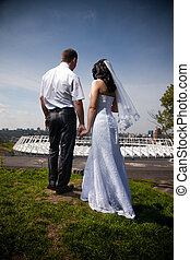 Newly married couple holding hands on top of hill