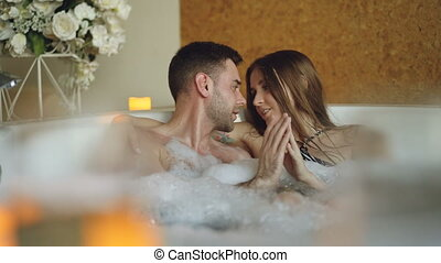 Newly married couple is relaxing in jacuzzi kissing,...
