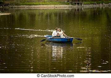 Newly married couple kissing on rowing boat in the middle of lake