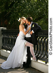 Portrait of a newly married couple kissing on a bridge