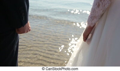 Newly married couple on tropical beach after sunset wedding, Romantic bride and groom
