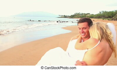 Newly married couple on tropical beach after sunset wedding...