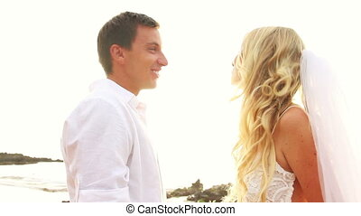 Newly married couple on tropical beach after sunset wedding,...