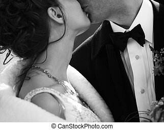 Newly-married couple - The groom and the bride kiss. b/w