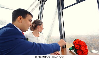 Newly married couple ridding on ferris wheel