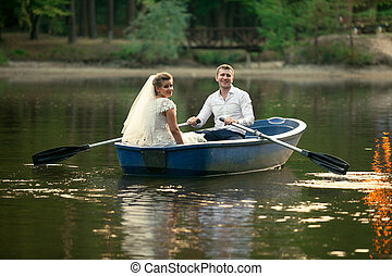 Newly married couple riding on wooden boat on lake
