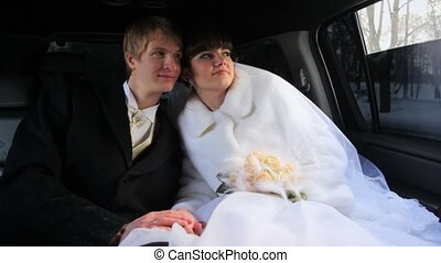 Newly-married couple sits in limousine having nestled to...