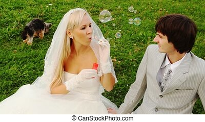 Newly-married couple sits near to doggie and bride starts up soap bubbles
