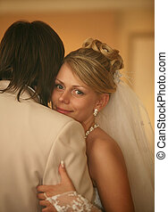Newly-married couple - Smiling bride gently embraces the...