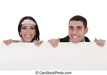 Newly married couple standing behind the board