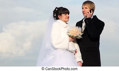 Newly-married couple stands nearby and man talks by cellular telephone