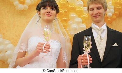 Newly-married couple stands together with champagne glasses