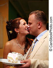 Newly married pair - Cheerful groom and the bride kiss, are...