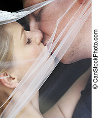 Newly married pair - The groom and the bride kiss having...