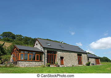 Newly restored residential stone barn with a slate roof in rural countryside against a blue sky.