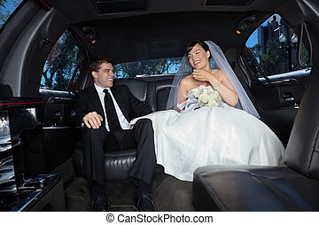 Newly wed couple in limousine - Bride and bridegroom in a...