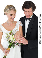 Newly wed couple looking at wedding rings - Newly wed couple...