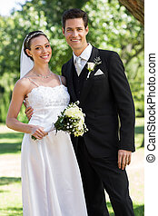 Newly wed couple standing in garden - Portrait of newly wed...