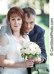 Newly wedding couple portrait, bride with flowers