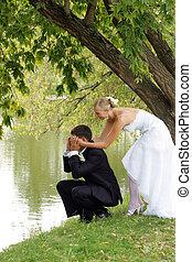 Newlyed couple by lake