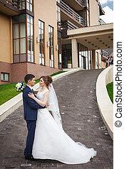 newlywed, összekapcsol dédelget, és, csókolózás, az ösvényen, ellen, építészet, közül, város