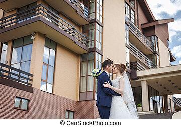 newlywed, összekapcsol dédelget, és, csókolózás, ellen, építészet, közül, város